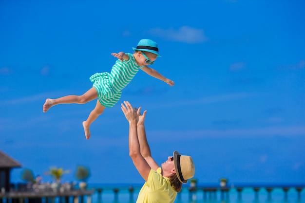 Papà felice divertendosi con la piccola figlia sulla spiaggia tropicale