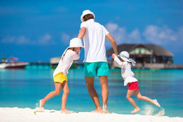Papà felice e adorabili bambine in spiaggia tropicale divertendosi