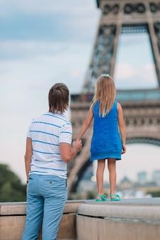 Papà felice e bambina adorabile che viaggiano a parigi vicino alla torre eiffel