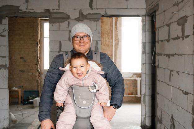 Papà felice e bambino nel vettore nella nuova casa sulla fase di rinnovamento