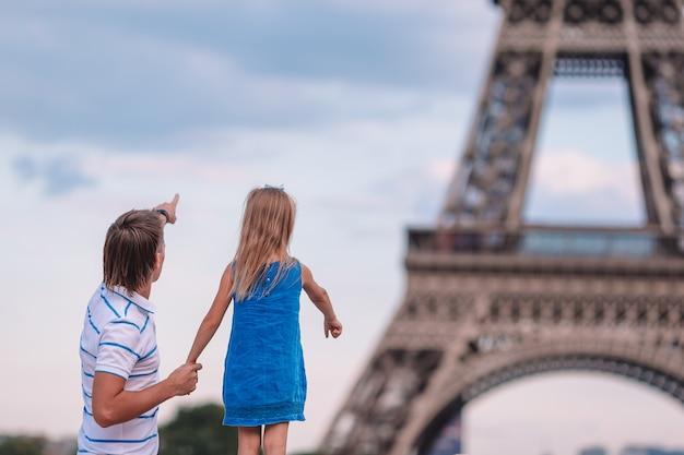 Papà felice e piccola ragazza adorabile che viaggiano a parigi vicino alla torre eiffel
