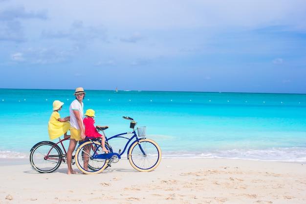 Papà felice e ragazze carine in sella a biciclette sulla spiaggia tropicale