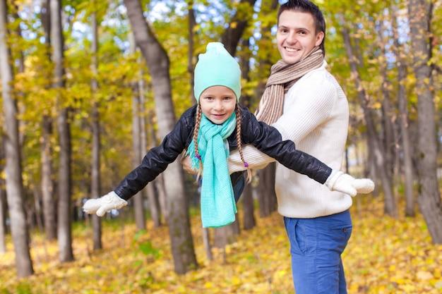 Papà felice e sua figlia piccola divertirsi nel parco in una giornata di sole autunnale