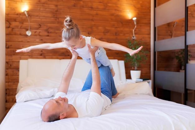 Papà gioca con sua figlia a casa. il padre prende una bambina. festa del papà