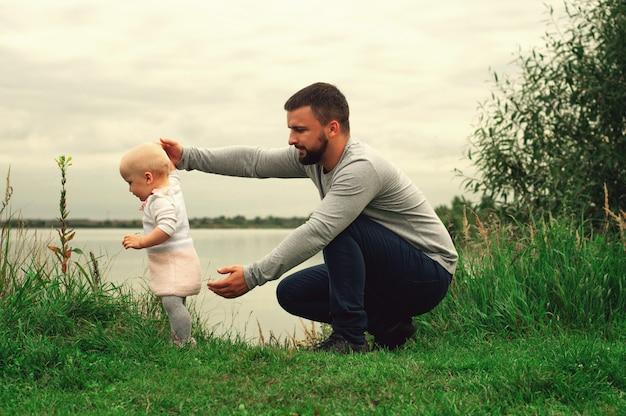 Papà insegna alla figlia a camminare nel parco, natura, erba. padre e figlia