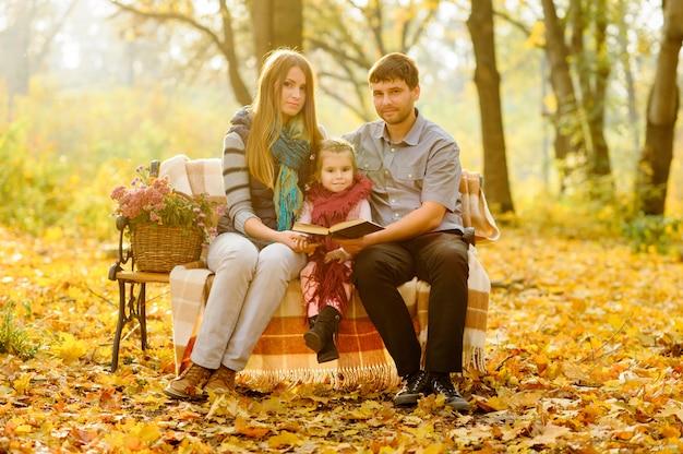 Papà, mamma e figlia sono seduti su una panchina nel parco in autunno. i genitori con una bambina si sono rifugiati in una coperta per scaldarsi.