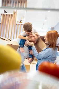 Papà mamma e figlio piccolo giocano in camera da letto con scatole di carta