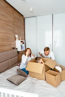 Papà, mamma e figlio piccolo giocano in camera da letto con scatole di carta