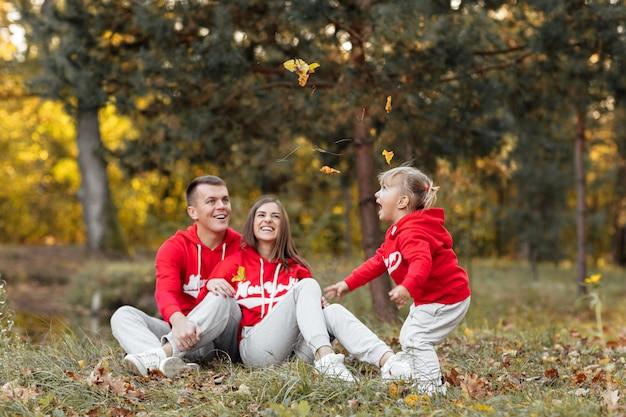Papà, mamma e piccola figlia carina divertendosi e giocando nel parco d'autunno.