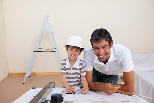 Papà sorridente e ragazzino che studiano architettura