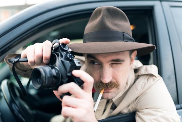 Paparazzo utilizzando la macchina fotografica d'epoca nella sua auto