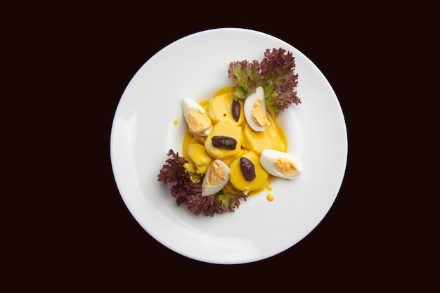 Papas huancaina, cibo tipico peruviano visto dall'alto sul tavolo di legno scuro.