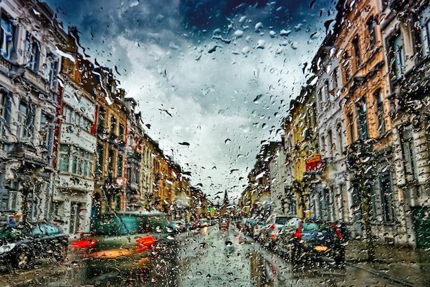 Parabrezza auto con gocce di pioggia durante la tempesta e semafori offuscati
