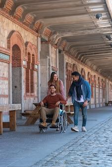 Paralizzato giovane su una sedia a rotelle accompagnato da un giovane e una donna che passeggia