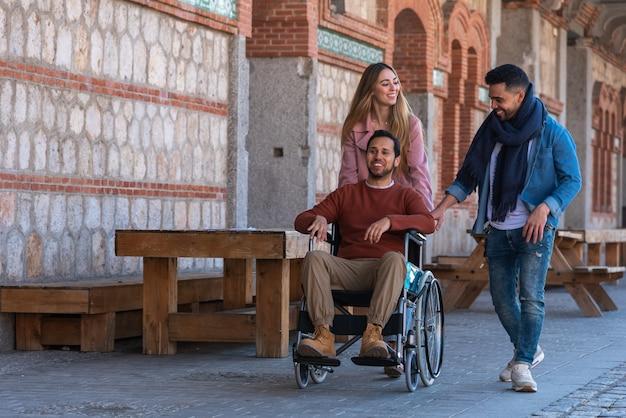 Paralizzato giovane su una sedia a rotelle accompagnato da un giovane e una ragazza che passeggiano