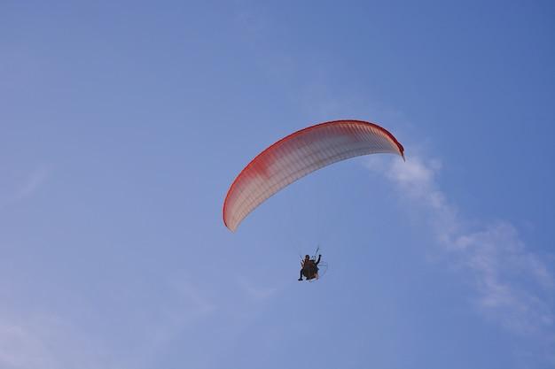 Paramotore (parapendio potenziato) con paracadute rosso-bianco che vola in cielo, sport estremo.