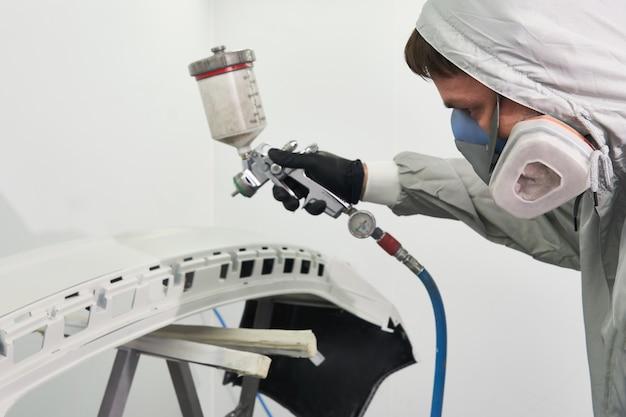 Paraurti della pittura del meccanico di un'automobile con lo spruzzatore nella cabina della pittura nel servizio automatico di riparazione
