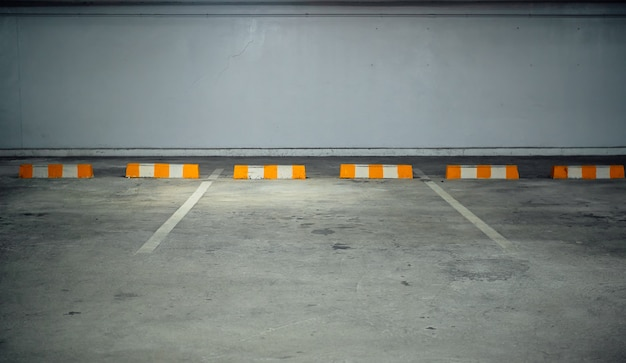 Parcheggio interno gratuito con barriere gialle bianche.