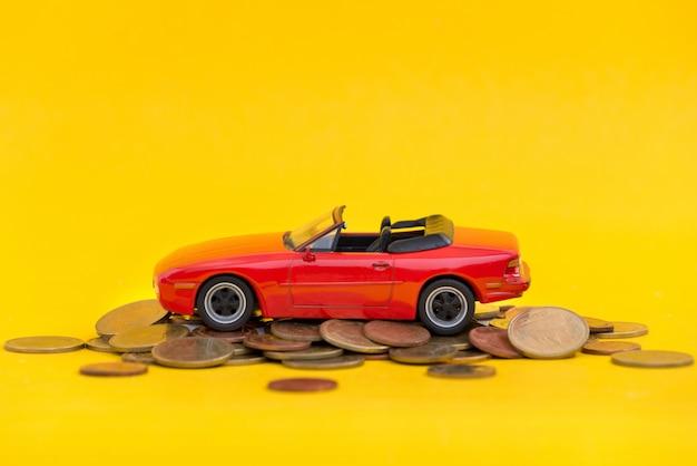 Parcheggio rosso di modello sulle monete dorate della pila