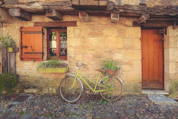 Parco della bicicletta di decolorazione nella porta di entrata anteriore della casa di pietra di tradizione nella città di bergerac, francia