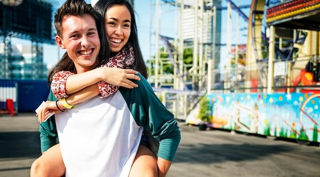Parco di divertimenti adolescente delle coppie che abbraccia concetto