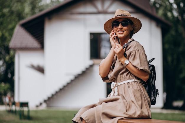 Parco di seduta della giovane donna facendo uso del telefono