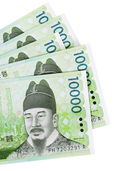 Parecchie fatture di valuta coreane 10.000 vinte completamente isolate contro bianco