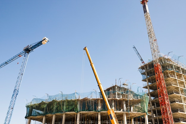 Parecchie gru davanti a costruzione contro cielo blu