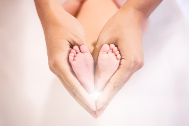 Parent holding nei piedi del neonato.