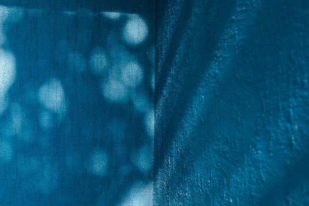 Parete blu brillante con ombra dagli alberi