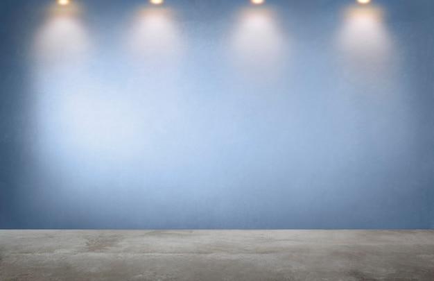 Parete blu con una fila di faretti in una stanza vuota