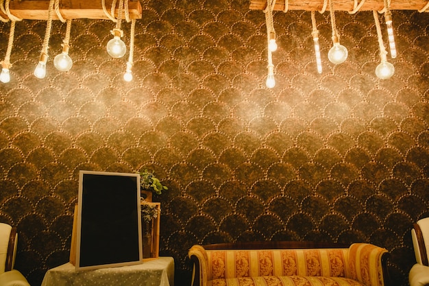 Parete calda decorata con lampadine e corde e spazio libero per inserire il testo in una cornice vuota