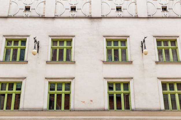 Parete con finestre in legno verdi in prospettiva. muro di facciata di edificio d'epoca. finestre arrotondate.