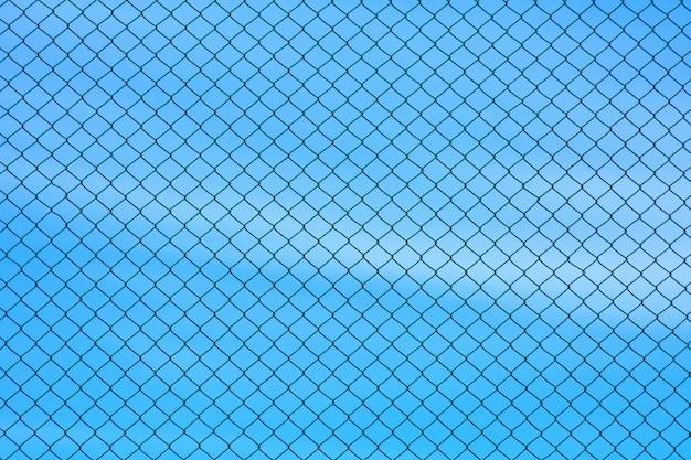 Parete del cavo metallico della gabbia su cielo blu
