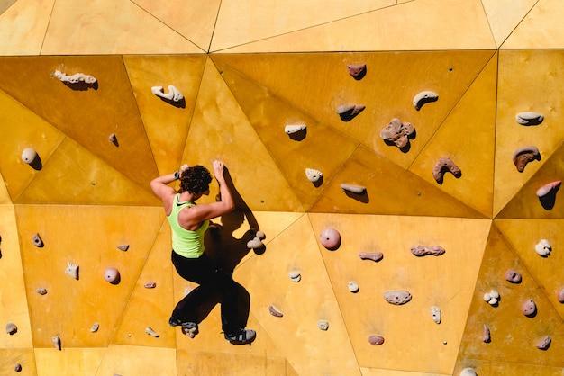 Parete di arrampicata con donna forte in buona forma facendo esercizio all'aperto