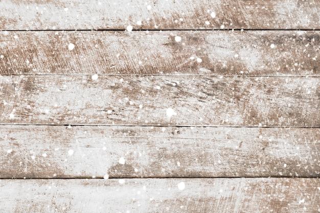 Parete di legno bianca d'annata con neve che cade. fondo rustico di natale, scena invernale.