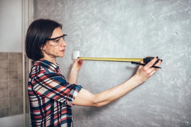Parete di misurazione della donna in cucina
