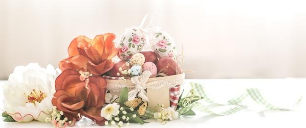 Parete di pasqua con cesto e uova con fiori