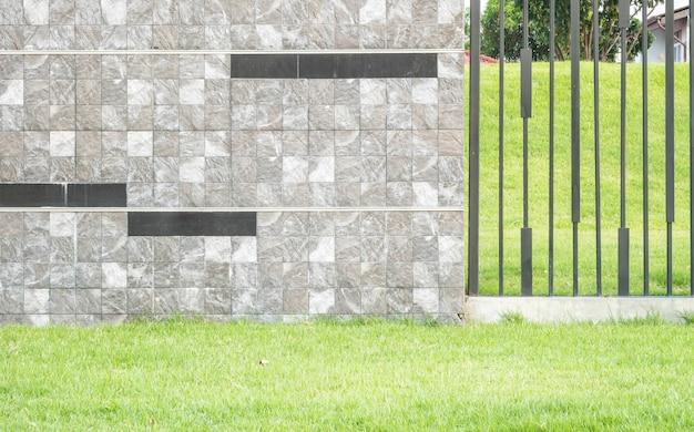 Parete di pietra del marmo del mattone di superficie del primo piano con il fondo di struttura dell'erba verde