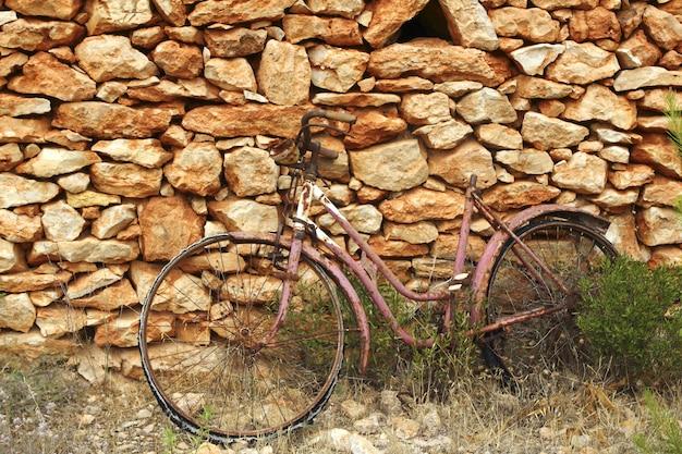 Parete di pietra dell'annata invecchiata della bicicletta stagionata