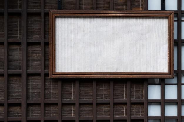 Parete e stuoia di legno giapponesi di vecchio stile dietro con una scatola di vecchio stile dell'etichetta del segno del libro bianco.
