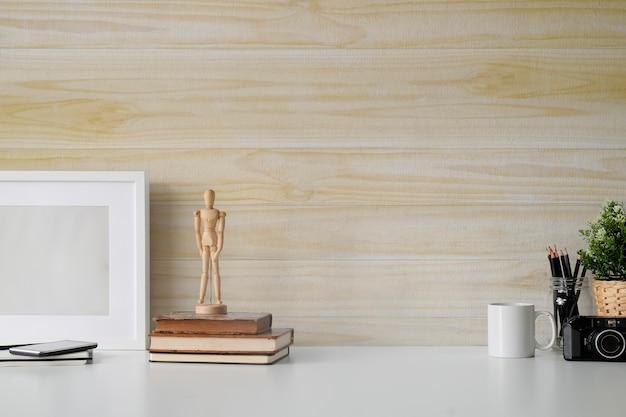 Parete in legno bianca con scrivania, tazza di caffè e accessori per artisti.