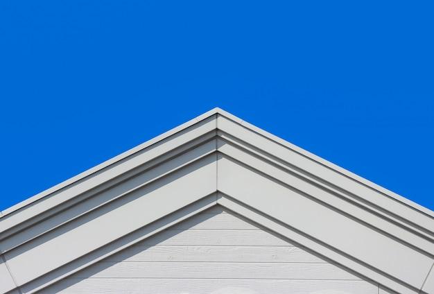 Parete moderna della facciata della casa di progettazione del tetto di timpano con il chiaro fondo del cielo blu.