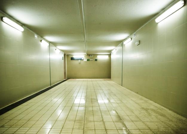 Parete piastrellata e tubi luminosi nella stazione della metropolitana