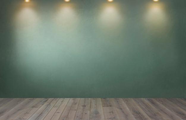 Parete verde con una fila di faretti in una stanza vuota