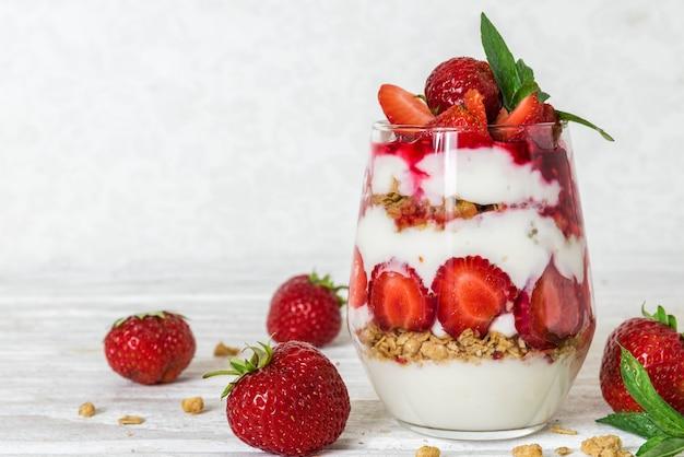 Parfait di yogurt fatto in casa con muesli e fragola in un bicchiere sul tavolo di legno bianco