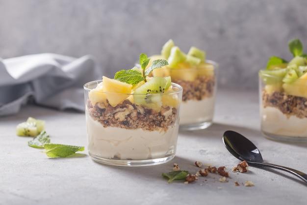 Parfait di yogurt fatto in casa con muesli, kiwi, ananas e noci in un bicchiere per una sana colazione su sfondo concreto