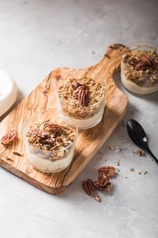 Parfait di yogurt naturale delizioso con caramello, noci pecan su sfondo conctere