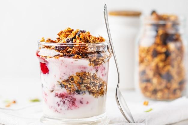 Parfait sano della prima colazione al forno del granola, dell'ostruzione e dello yogurt in vetro.