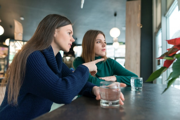 Parlando di giovani donne, ragazze seduti nel caffè sorridendo e parlando, bere acqua pulita in vetro